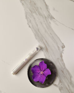 doTERRA Anti-Ageing Eye Cream with a purple flower in a gray ceramic plate on a white marble background.