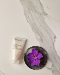 doTERRA Invigorating Scrub with a purple flower in a gray ceramic plate on a white marble background.