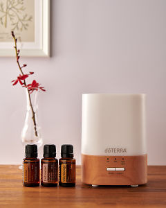 doTERRA Lumo diffuser with Cassia, Cedarwood and Wild Orange essential oils on a side table.