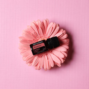 doTERRA Passion sitting on a pink flower on a pink textured background.