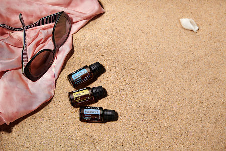 doTERRA Ylang Ylang, Lemon and Peppermint with sunglasses and a pink silk scarf on the beach.
