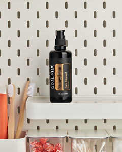 doTERRA Yarrow|Pom Body Renewal Serum on a bathroom shelf with additional doTERRA products and bathroom accessories.
