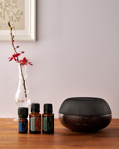 doTERRA Brevi Walnut diffuser with Deep Blue, AromaTouch and Balance essential oils on a side table.