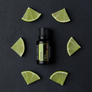 doTERRA Lime oil and lime pieces on black concrete background.