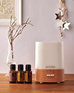 doTERRA Lumo diffuser with Geranium, Lemon and Wild Orange essential oils and holiday decorations on a side table.