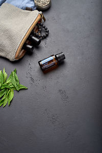 doTERRA DigestZen with clutch, accessories and mint leaves on a black concrete background.