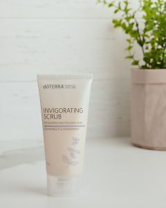 doTERRA Essential Skin Care Invigorating Scrub sitting on a white bench near a pot plant.