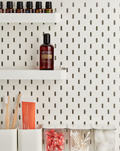 doTERRA Fractionated Coconut Oil on a bathroom shelf with additional doTERRA products and bathroom accessories.