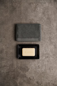 doTERRA Spa Moisturizing Bath Bar in a black soap dish with a gray towel on a gray stone bathroom bench.