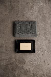 doTERRA Spa Moisturizing Bath Bar in a black soap dish with a gray towel on a gray stone bathroom bench.