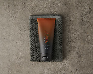 doTERRA Amavi After Shave Lotion and gray washcloth on a gray stone background.