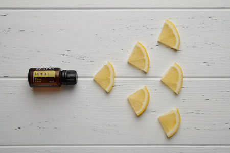 doTERRA Lemon oil and lemon pieces on white rustic wooden background.