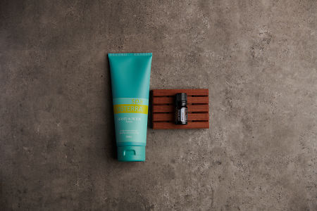 doTERRA Spa Hand and Body Lotion with Melissa essential oil on a stone background.