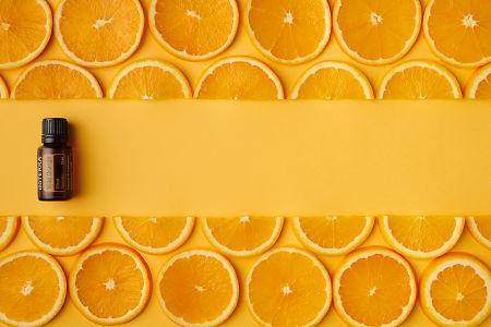 doTERRA Wild Orange oil and orange slices on orange paper background.