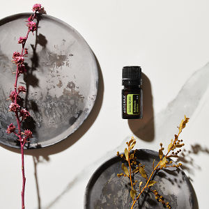 doTERRA Lemon Myrtle with plants on ceramic plates on a white marble background.