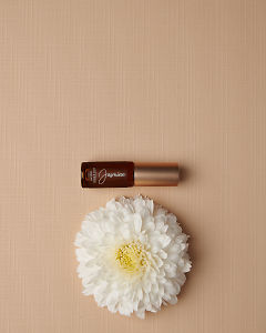 doTERRA Jasmine Touch 4ml and a white flower on a tan linen textured background.