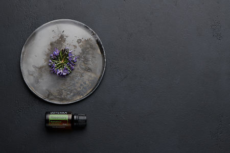doTERRA Rosemary with rosemary flowers on a ceramic plate on a black concrete background.