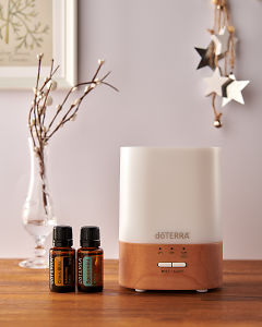 doTERRA Lumo diffuser with Citrus Bliss and Spearmint essential oils and holiday decorations on a side table.