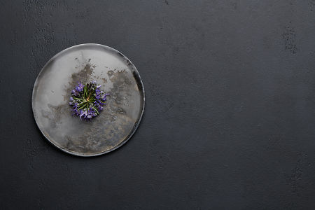 Rosemary flowers on a ceramic plate on a black concrete background.