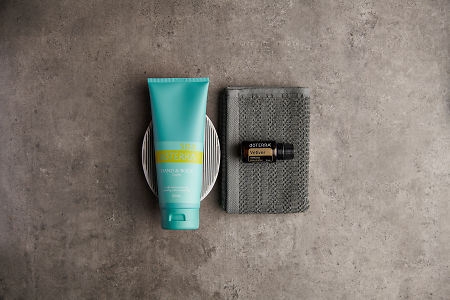 doTERRA Spa Hand and Body Lotion with Vetiver essential oil with bathroom accessories on a stone background.
