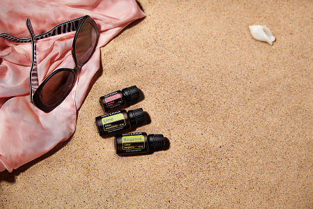 doTERRA Passion, Lime and Bergamot with sunglasses and a pink silk scarf on the beach.