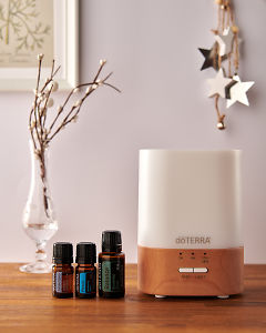 doTERRA Lumo diffuser with Juniper Berry, Peace and Balance essential oils and holiday decorations on a side table.