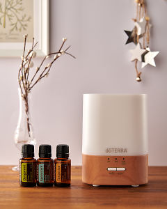 doTERRA Lumo diffuser with Bergamot, Spearmint and Tangerine essential oils and holiday decorations on a side table.