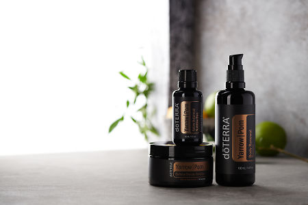 doTERRA Yarrow Pom Collection on a bench in a rustic setting near a window.