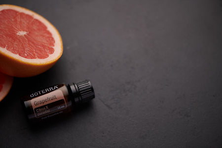 doTERRA Grapefruit oil and grapefruit pieces on black concrete background.