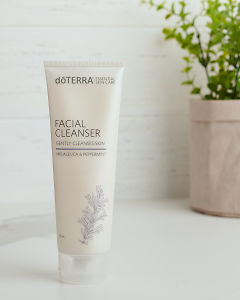 doTERRA Essential Skin Care Facial Cleanser on a white bench near a pot plant.