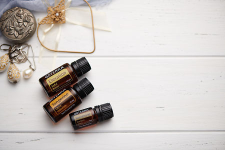 doTERRA Elevation, Tangerine and Sandalwood oils with romantic jewellery on a white vintage wooden background.