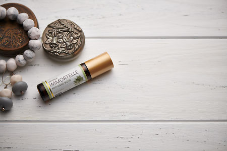 doTERRA Immortelle blend, jewellery and trinkets on white rustic wooden background.