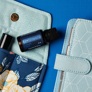 doTERRA Adaptive on an essential oil bag with a diary on a blue textured background.
