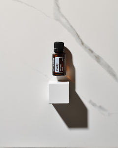 doTERRA Purify essential oil blend above a white wooden block in direct sunlight on a white marble background.