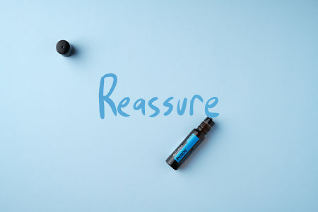 "doTERRA Peace Touch on a light blue colored background with hand written ""Reassure""."