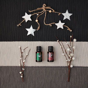 doTERRA Holiday Joy and Holiday Peace with holiday decorations on a dark, medium and light gray textured background.