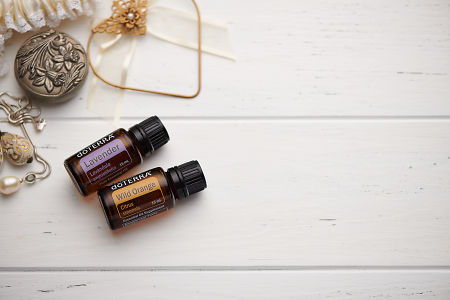 doTERRA Lavender and Wild Orange oils and wedding accessories on white rustic wooden background.