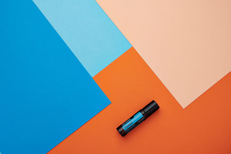 doTERRA Peace Touch on a blue and orange geometric background.