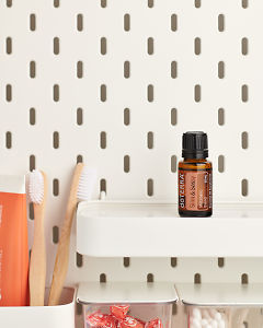 doTERRA Slim and Sassy Metabolic Blend on a bathroom shelf with additional doTERRA products and bathroom accessories.