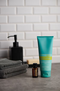 doTERRA Spa Hand and Body Lotion and Vetiver essential oil with bathroom accessories on stone bench
