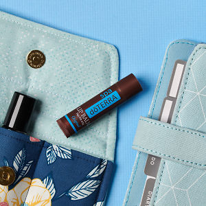 doTERRA Spa Original Lip Balm on an essential oil bag with a diary on a blue textured background.