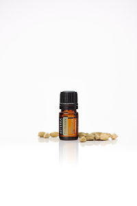doTERRA Cardamom with cardamom pods on a white background with reflection.
