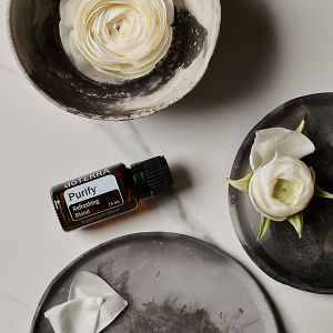 doTERRA Purify essential oil with flowers on ceramic dishes on a grey stone background.