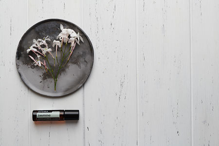 doTERRA Jasmine Touch with jasmine flowers on a ceramic plate on a white wooden background.