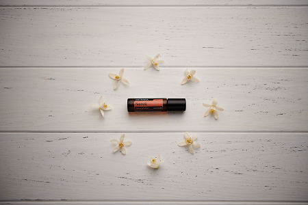 doTERRA Neroli Touch circled by orange blossoms on a white wooden background.