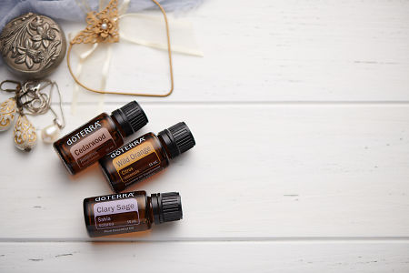 doTERRA Cedarwood, Wild Orange and Clary Sage oils with romantic jewellery on a white vintage wooden background.