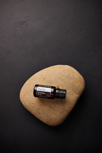 doTERRA Purify sitting on a stone on a black concrete background.