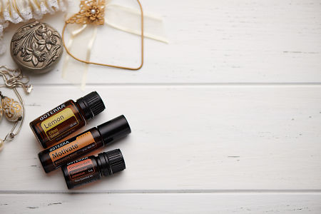 doTERRA  Lemon, Motivate Touch and Cinnamon oils and wedding accessories on white rustic wooden background.