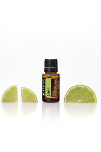 doTERRA Lime with lime slices on a white background with reflection.
