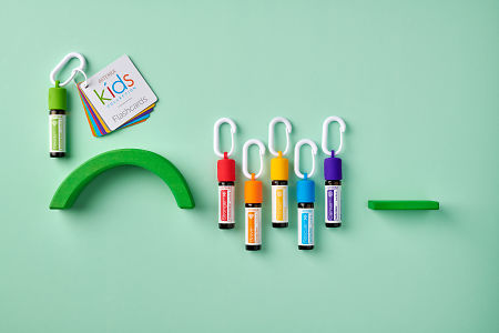 doTERRA Kids Oil Collection  oils with caps and carabiners and flashcards, featuring Steady, on a pale green paper background.